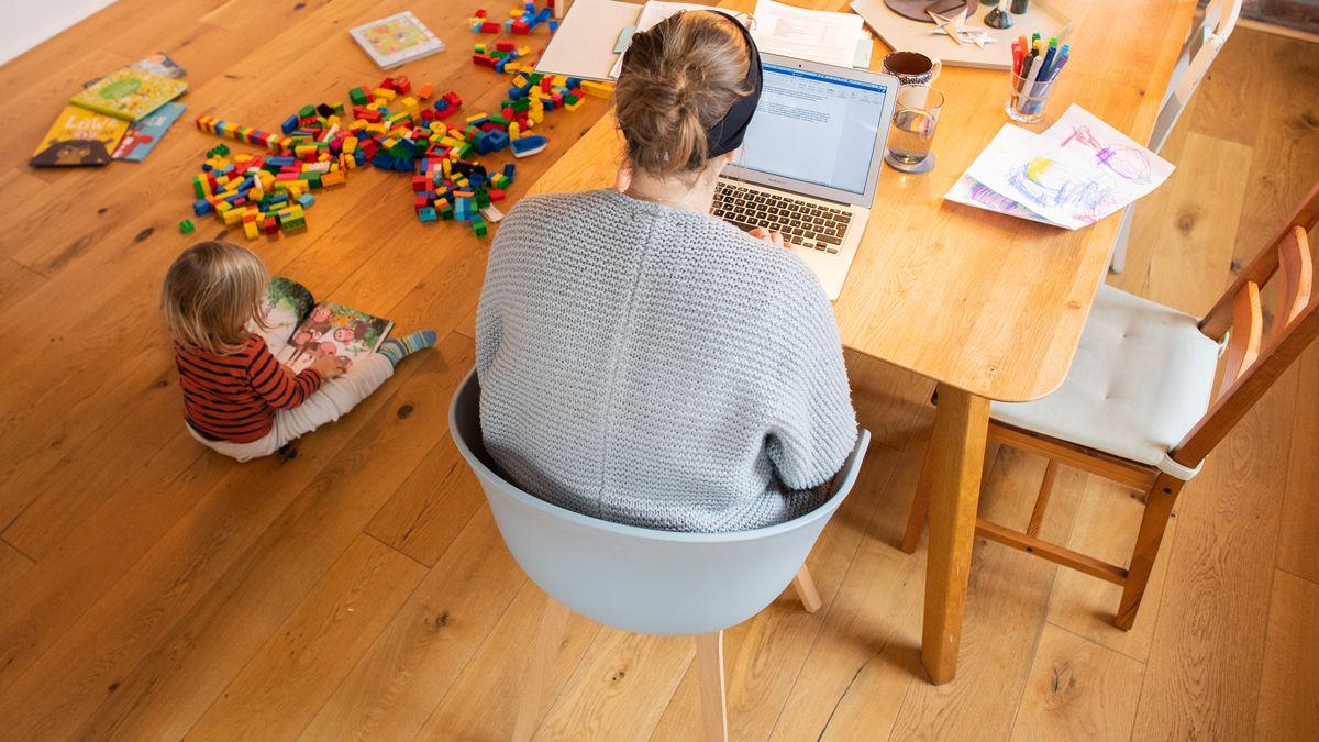 Mutter sitzt an einem Tisch, Kind spielt daneben auf dem Boden