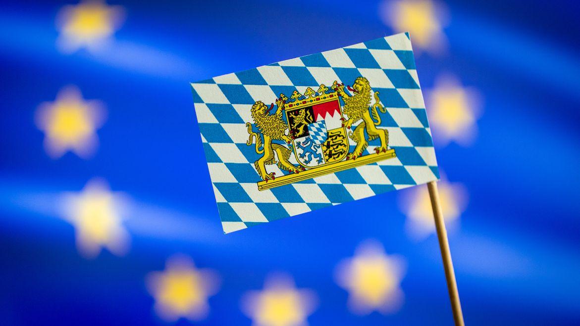 Eine bayerische Flagge vor der EU Flagge.
