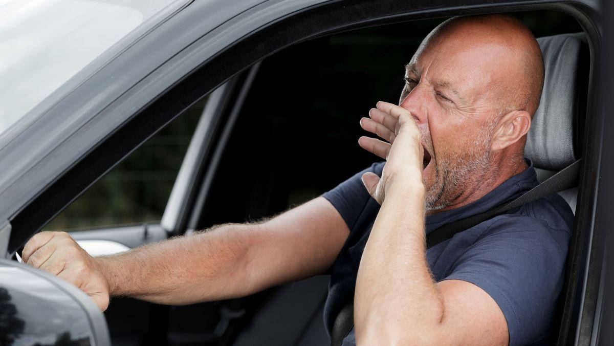 Mann sitzt im Auto und gähnt