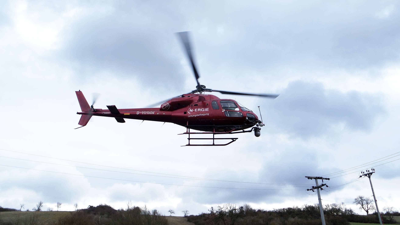 Hubschrauber der N-ERGIE Aktiengesellschaft überfliegt Stromleitungen.