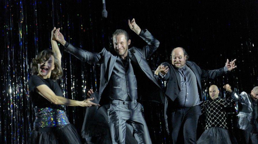 Eine Frau und mehrere Männer tanzen, ganz in schwarz, vor einem Glitzervorhang über die Bühne und halten sich dabei an den Händen