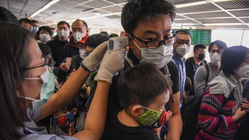 Eine Mitarbeiterin des Flughafens Hang Kong misst bei einem Fluggast Fieber. Die meisten der Fluggäste tragen Atemmasken.   Bild:picture alliance/Pacific Press Agency