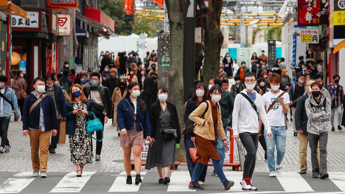 Maskentragende Menschen auf einer belebten Straße in Tokyo.