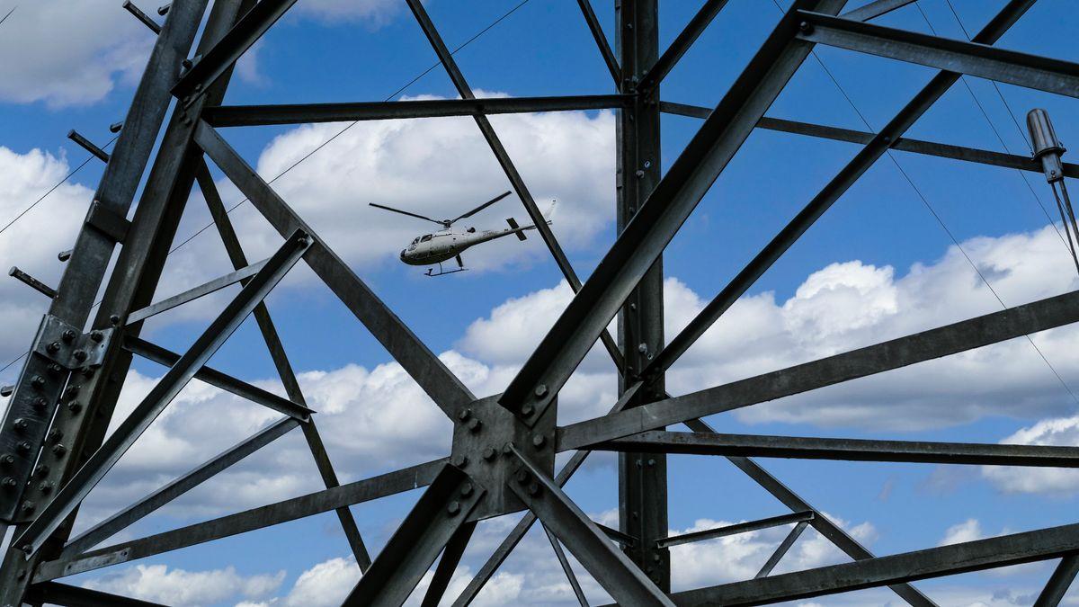 Ein Helikopter fliegt über eine Stromleitung.