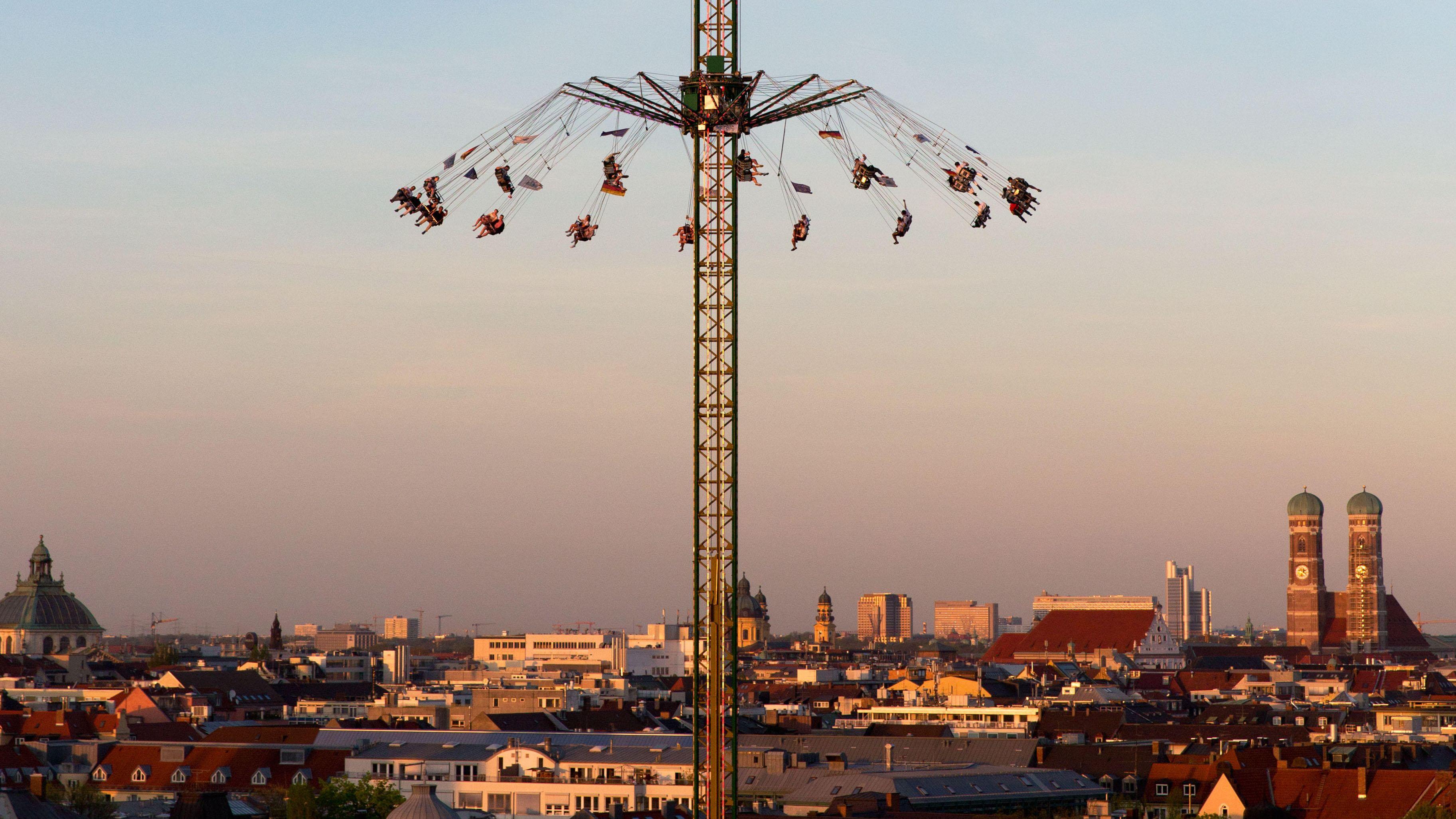 Besucher des Oktoberfests schweben im Kettenkarussell über München