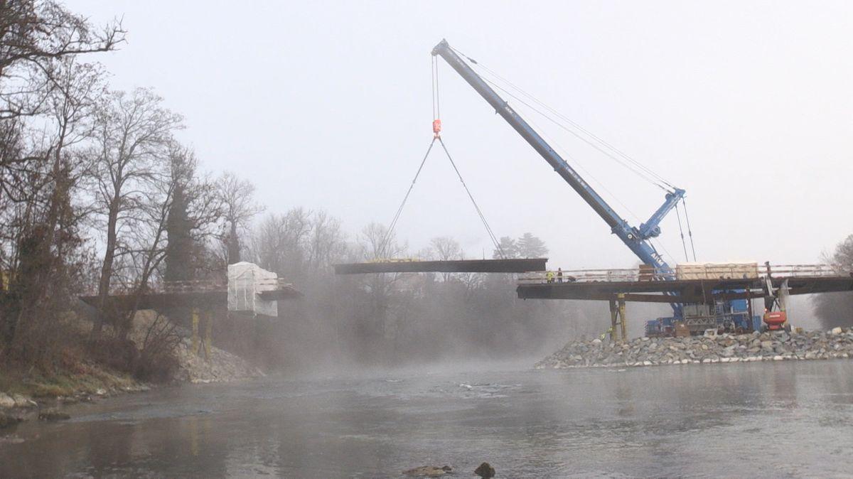 Ein Kranarm hängt ein etwa 20 Meter langes Brückenteil in eine verbliebene Lücke über dem Lech ein.