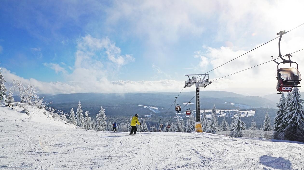 Skifahrer auf einer Piste neben einem Sessellift