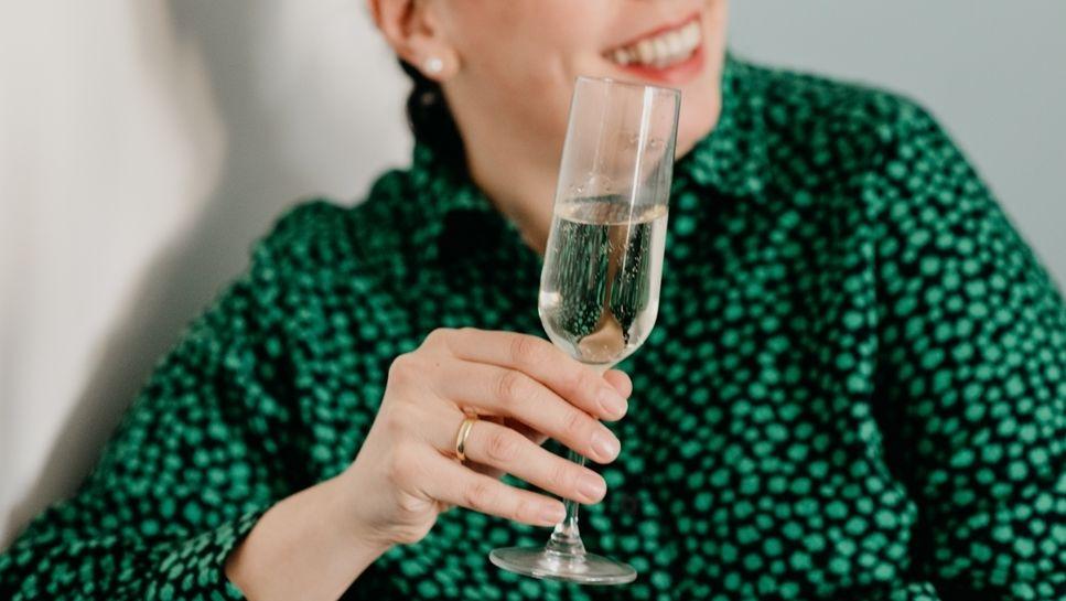 Alkohol - oft ein Grund für Corona-Verstöße. Symbolbild  - Eine Frau im grünen Kleid hat ein Glas Sekt in der Hand.