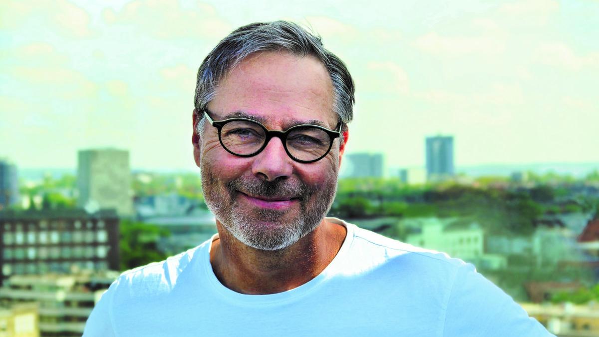 Ein Mann mit Brille schaut lächelnd in die Kamera.