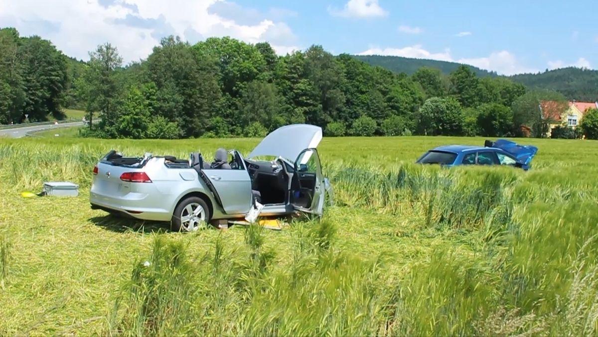 Zwei verunglückte Autos stehen auf einem Feld.