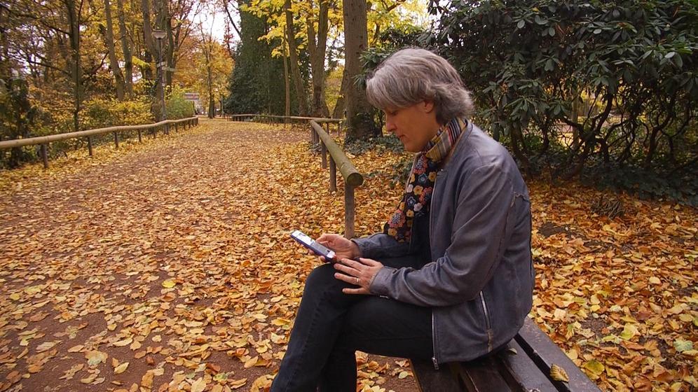 Eine Frau sitzt auf einer Parkbank | Bild:BR/ Tillman Kleinjung