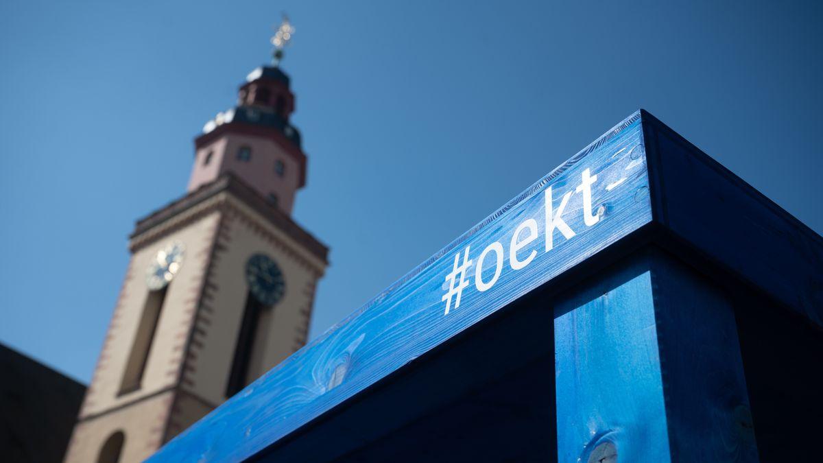#oekt steht am ersten Tag des 3. Ökumenischen Kirchentags auf der Installation, einem großen Tisch, vor der St. Katharinenkirche in Frankfurt am Main.