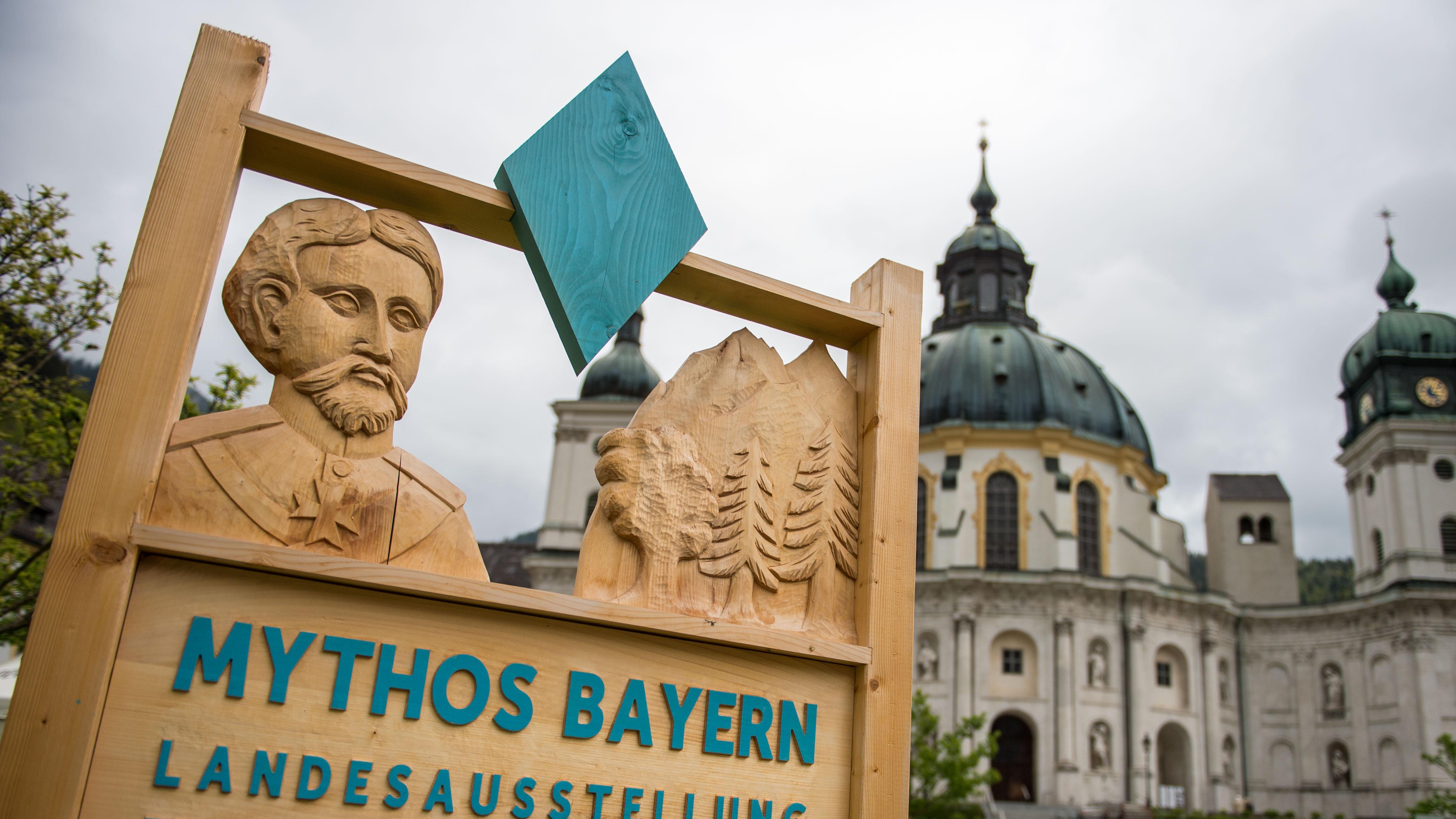 """Aus Holz geschnitztes Hinweisschild der Landesausstellung """"Mythos Bayern"""" im Kloster Ettal"""