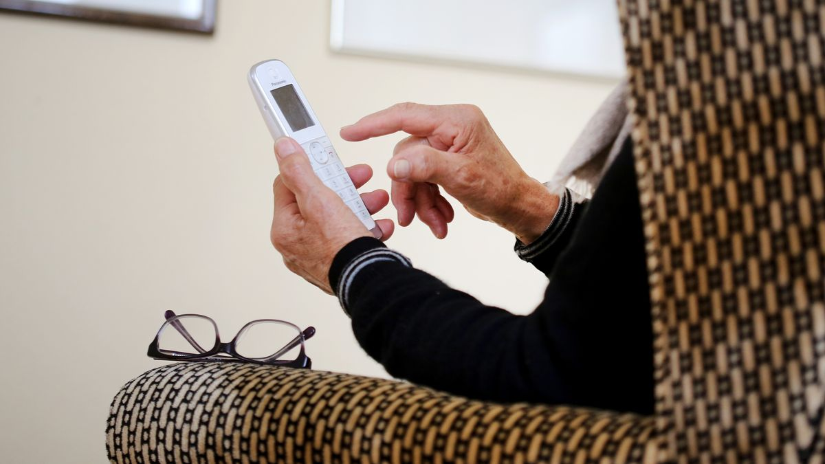 Eine ältere Dame nimmt in ihrer Wohnung ein Telefongespräch an (Symbolbild)