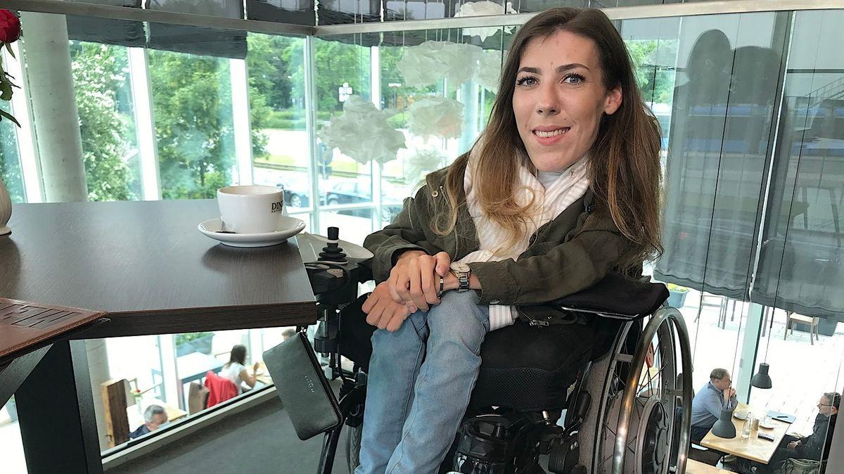 Frau sitzt in Rollstuhl und trinkt Kaffee