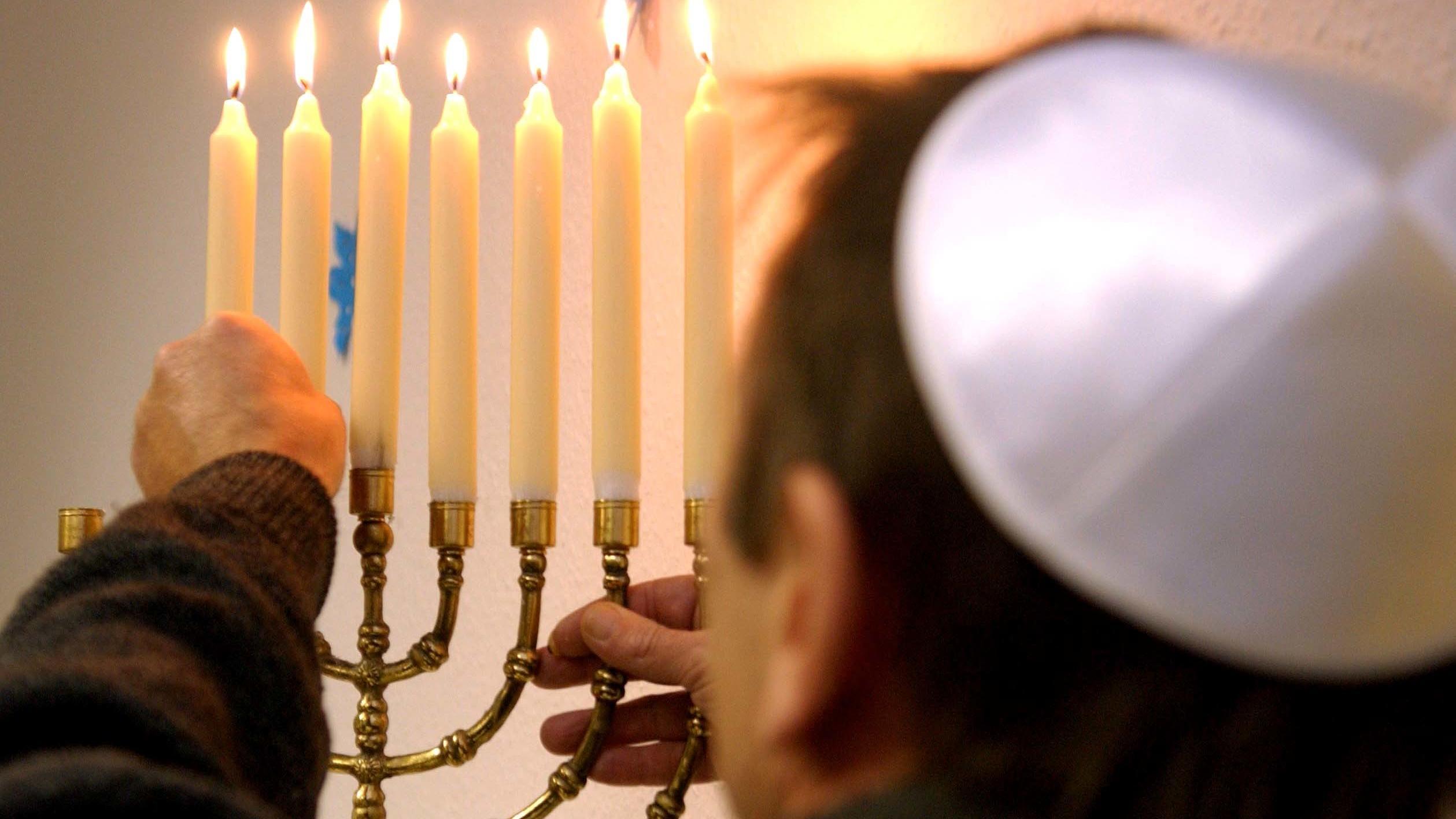 Mitglied einer Jüdischen Gemeinde entzündet die Kerzen auf einem Chanukka-Leuchter