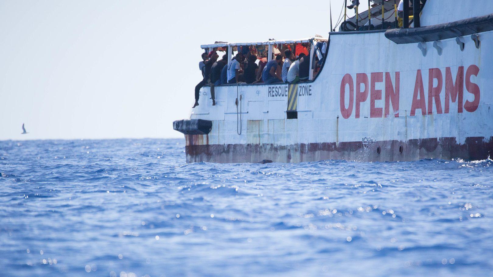 """Aus dem Meer gerettete Migranten sitzen auf dem Deck des Rettungsschiffes """"Open Arms""""."""