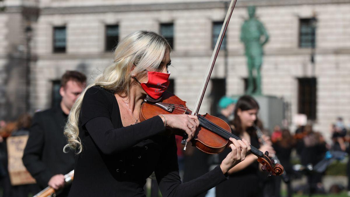 Eine Frau mit Mundschutz spielt Geige, hinter ihr unscharf weitere Musiker (Symbolbild)