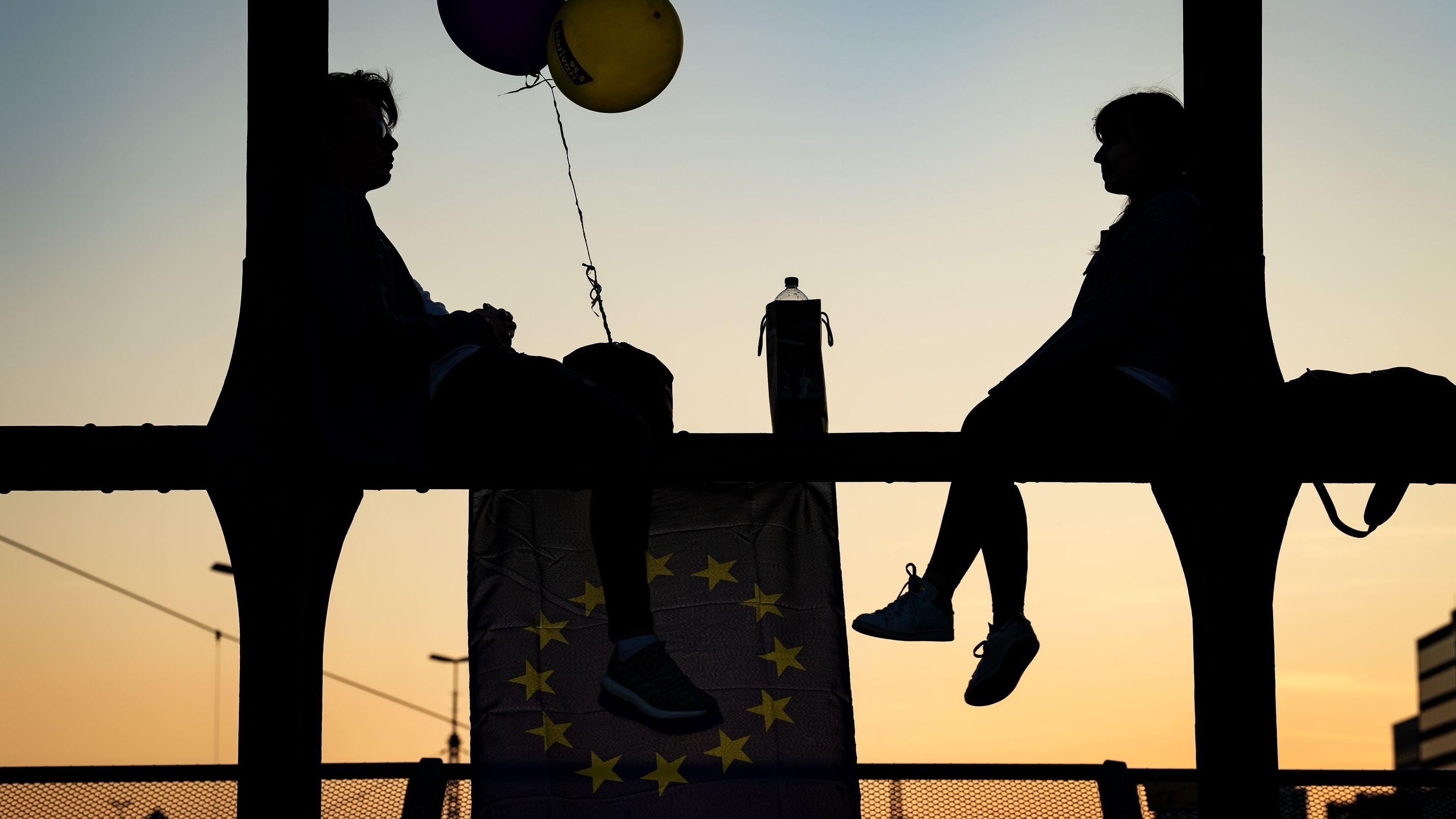 Ein junger Mann und eine junge Frau sitzen mit Luftballons und einer Europaflagge auf den Streben einer Brücke