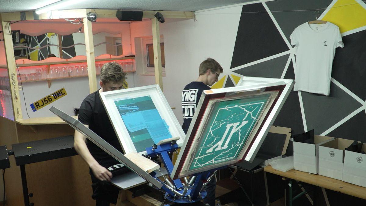 Felix Homann druckt ein T-Shirt, Conrad Braun verpackt die Ware