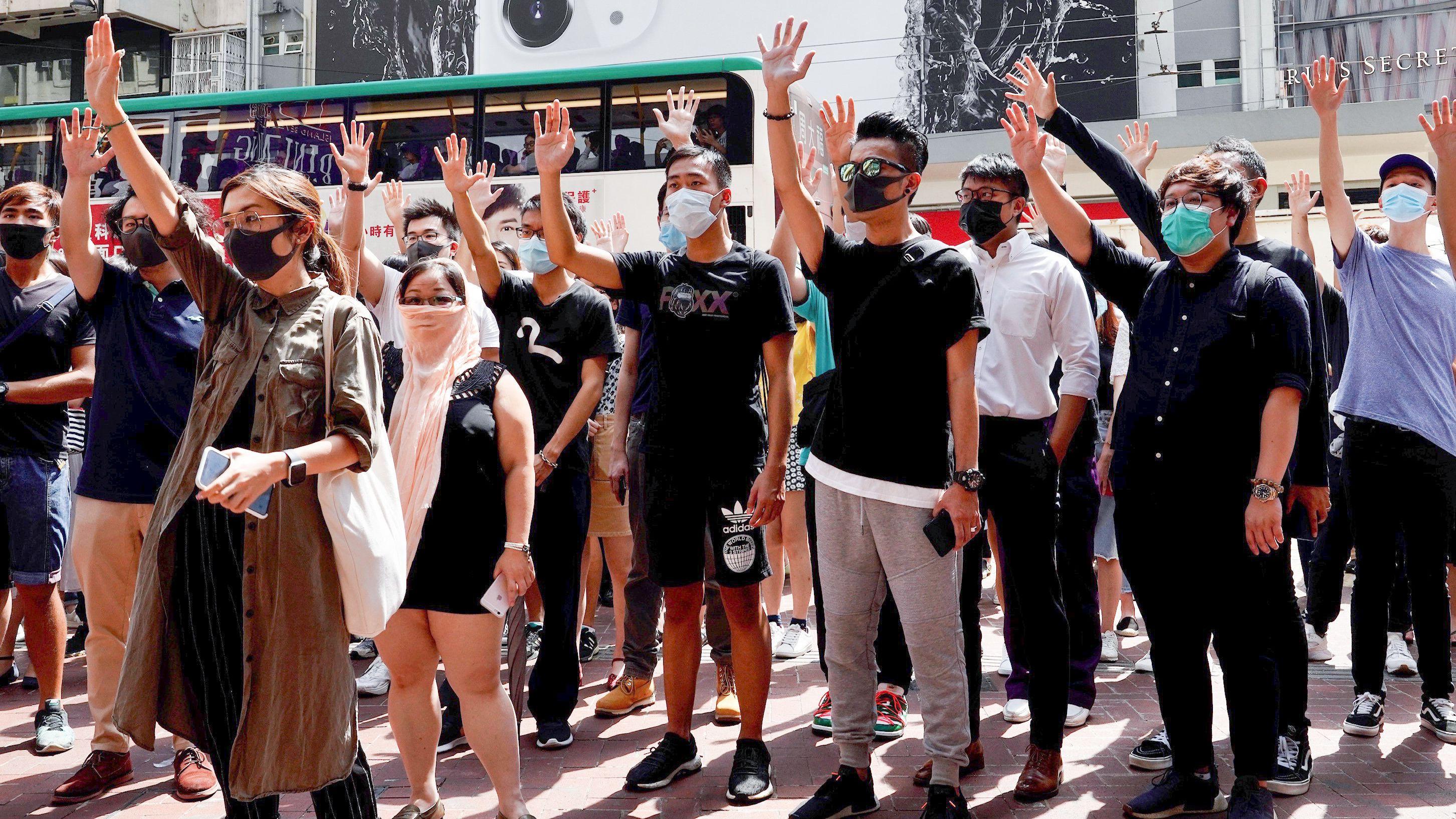 Hong Kong: Demonstranten mit Masken halten die Hände hoch, um ihre fünf Forderungen zu vertreten.