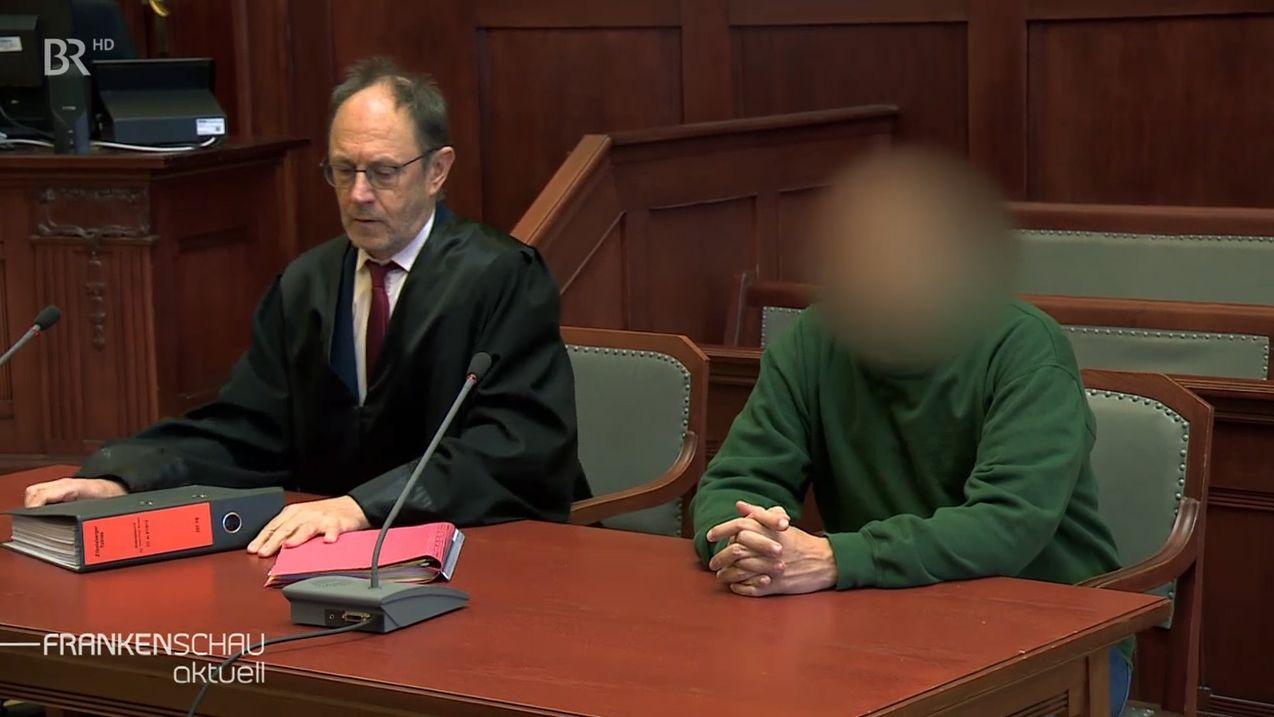 Ein verpixelter Angeklagter sitzt neben seinem Anwalt auf der Anklagebank im Gerichtssaal.