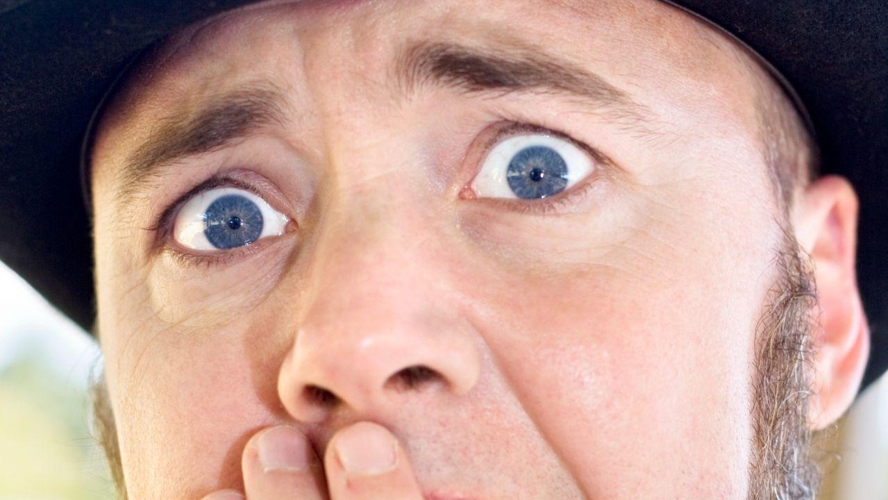 Erschrockener Mann mit aufgerissenen blauen Augen