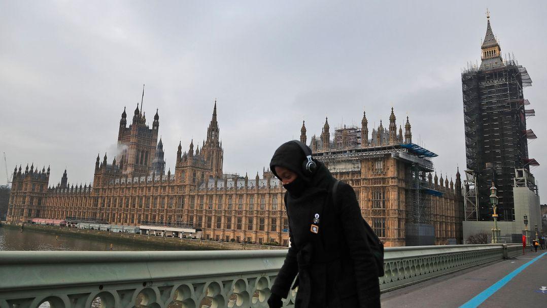 London: Eine Frau mit einer Schutzmaske geht über die Westminster Bridge