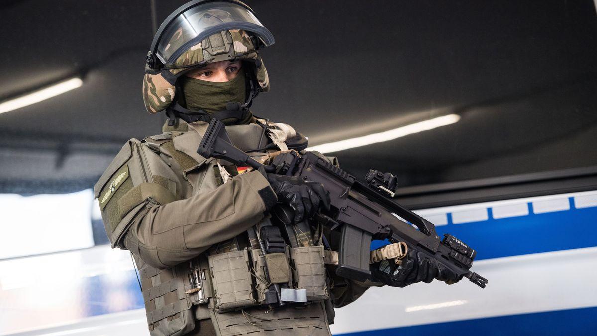 Ein SEK-Beamter steht mit seiner Ausrüstung vor einem Polizeifahrzeug.