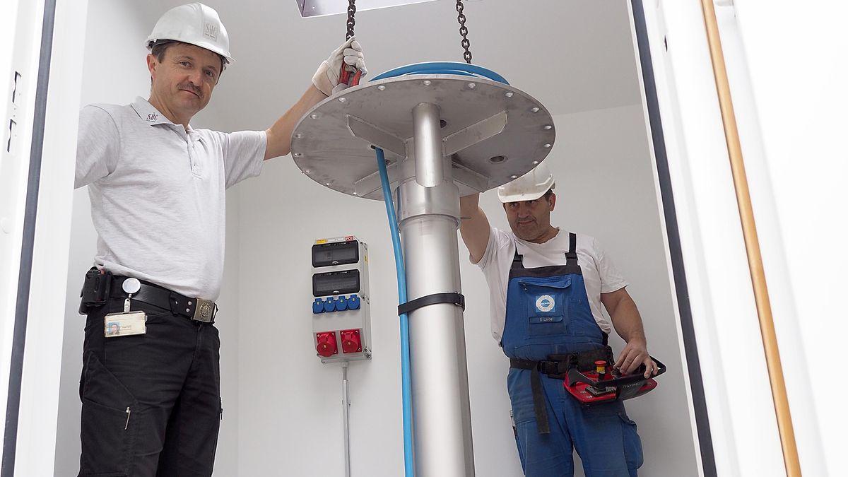 Zwei Mitarbeiter der Coburger Stadtwerke lassen eine Rohr, des an zwei Eisenketten hängt, in die Tiefe.