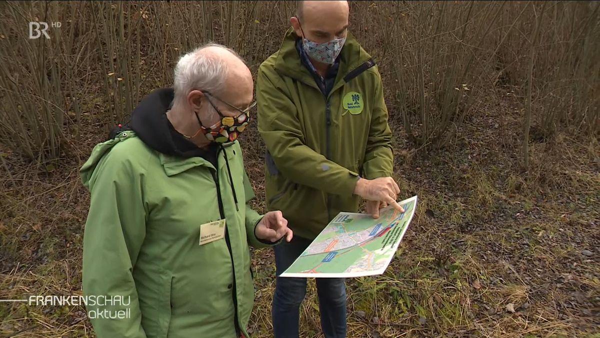 Zwei Mitglieder des Bund Naturschutz betrachten im Wald eine Karte