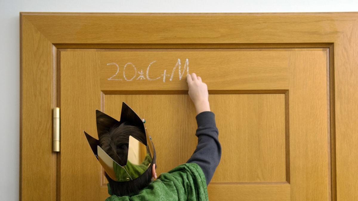Ein Sternsinger schreibt C+M+B an eine Türe.
