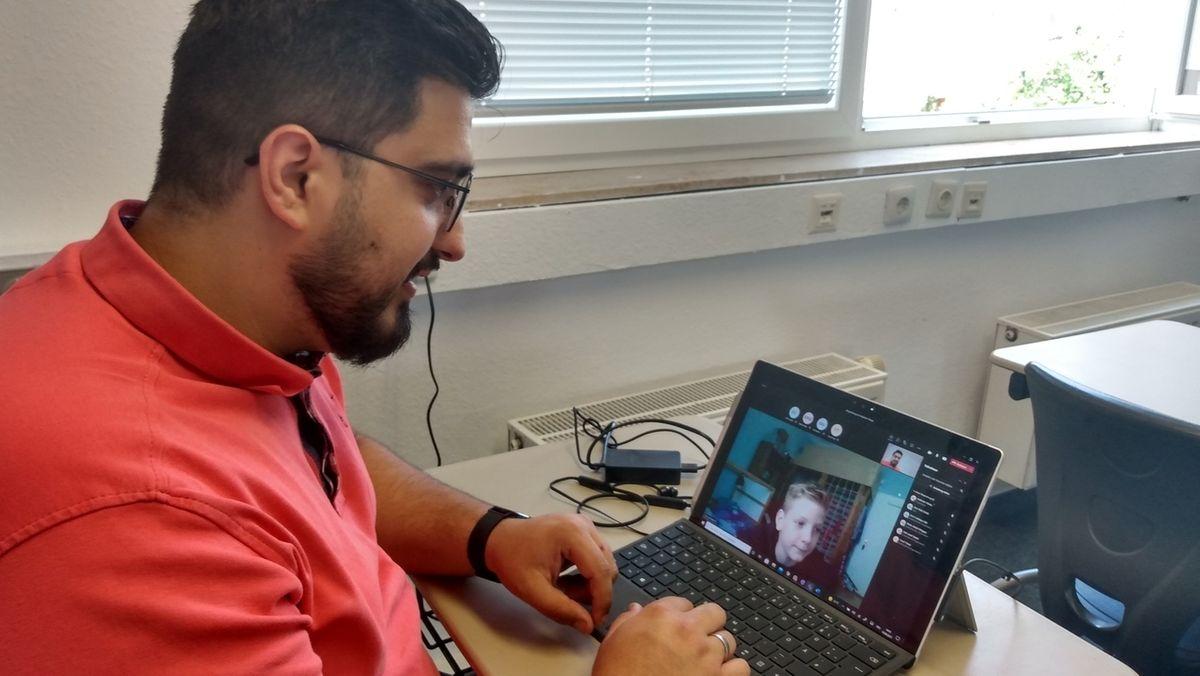 Mehmet Yilmaz vom Global Elternverein vor einem Laptop bei einer Teamskonferenz.