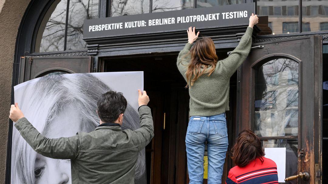 """Eine Frau befestigt über einem Theatereingang ein Schild mit der Aufschrift """"Perspektive Kultur: Berliner Pilotprojekt Testing"""""""