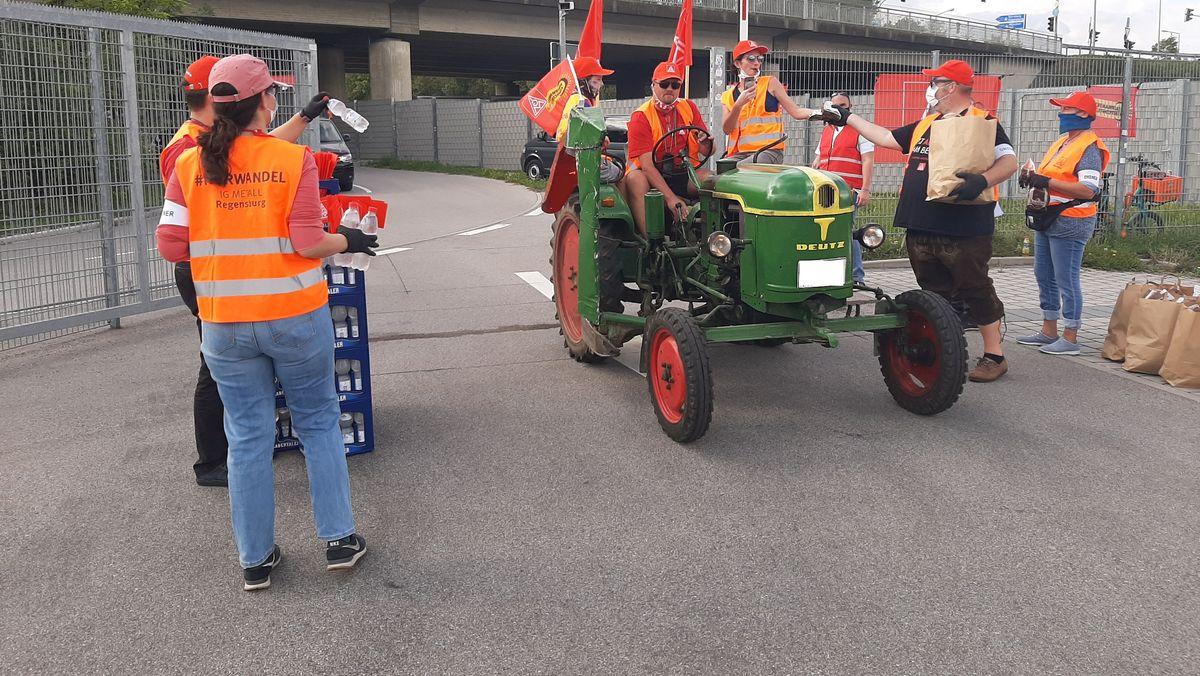 Ein alter Traktor, besetzt mit Protestierenden, fährt in Richtung Jahn-Stadion