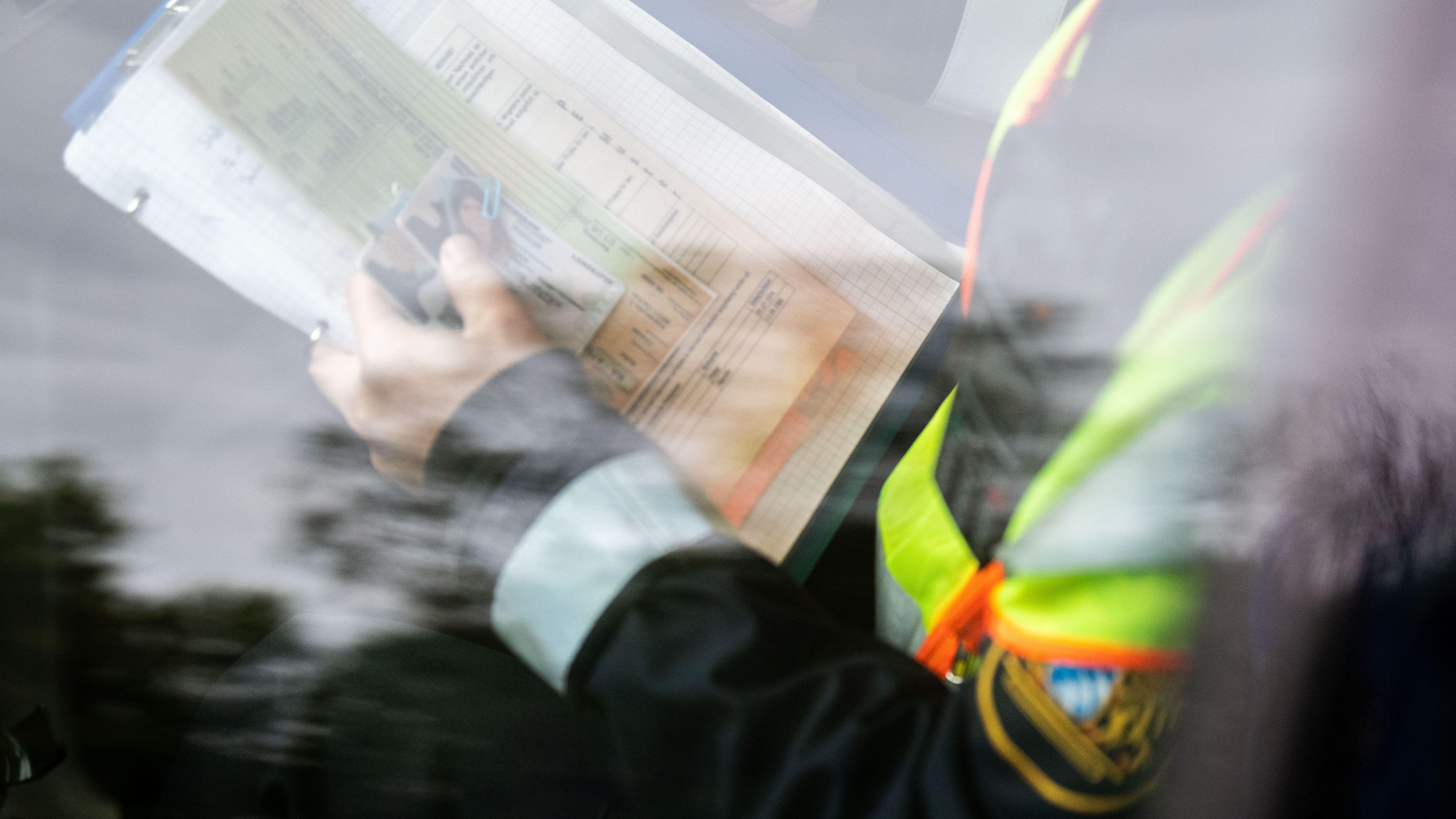 Die Personalien (Szene von einer Polizeischule, Musterpapiere) werden von einer Polizistin in einem Streifenwagen kontrollier