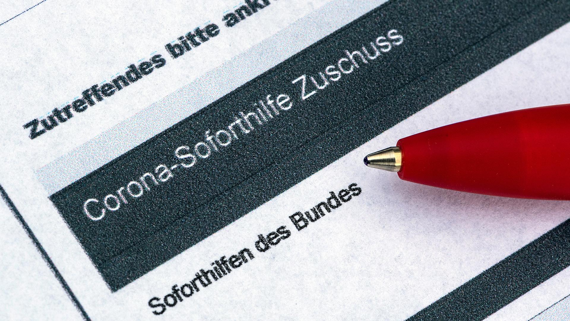Ein Stift liegt auf einem Antrag auf Corona-Soforthilfe Zuschuss