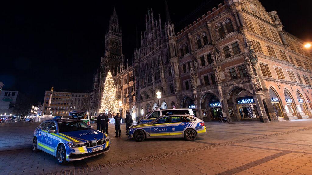 Polizisten stehen auf dem ansonsten menschenleeren Marienplatz im Zentrum der Stadt. Auch an Silvester galt in Bayern die nächtliche Ausgangsbeschränkung ab 21.00 Uhr.