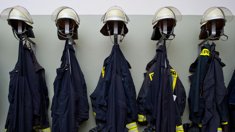 Feuerwehranzüge und Helme hängen an Garderobehaken (Symbolbild)