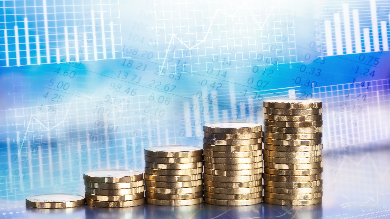 Ansteigende Stapel mit Münzen und Diagrammen und Charts im Hintergrund