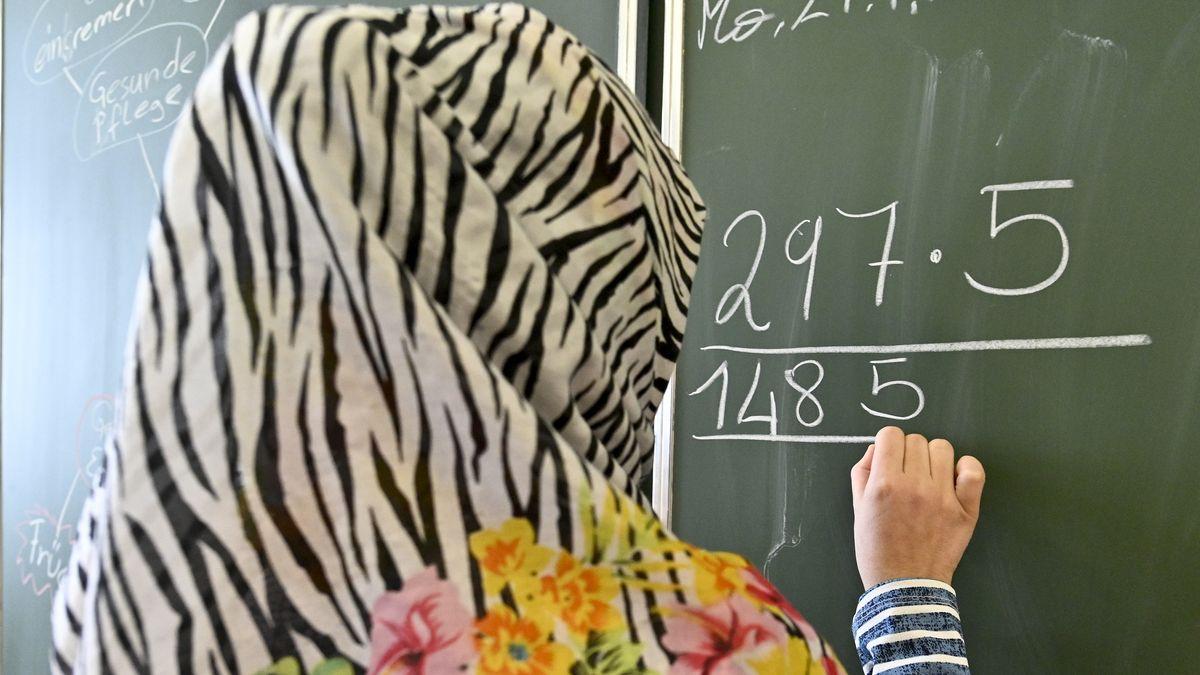 Eine Frau mit Kopftuch steht in der Schule an einer Tafel und schreibt (Symbolbild)