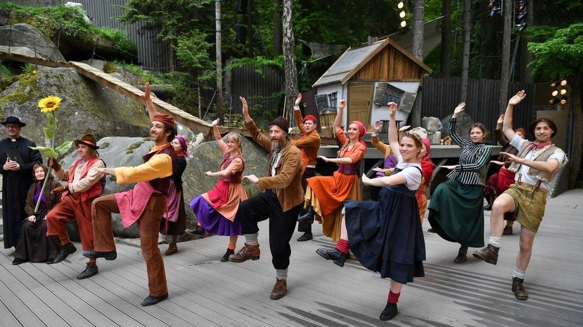 Bunt gekleidete Schauspieler und Schauspielerinnen tanzen auf der Freilichtbühne von Wunsiedel.