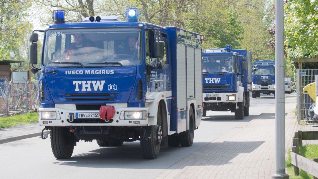 Drei Einsatzfahrzeuge des Technischen Hilfswerks fahren hintereinander auf einer Straße.