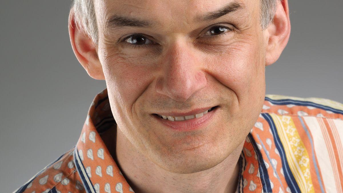 Christoph Noll im bunt gestreiften Hemd lächelt in die Kamera.