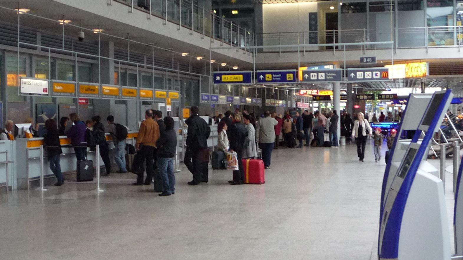 Fluggäste mit Koffern vor Schaltern in der Abflughalle am Airport Nürnberg