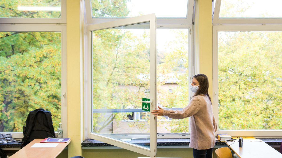 Eine Schülerin öffnet in einer Klasse das Fenster.