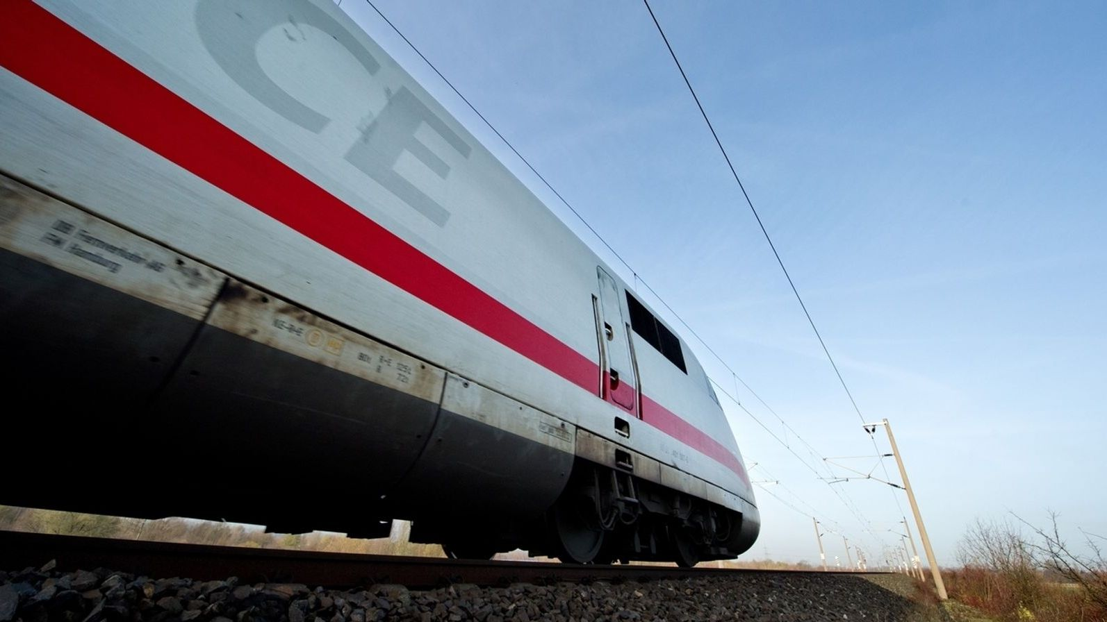 Ein Zug fährt auf einem Gleis, im Hintergrund blauer Himmel.