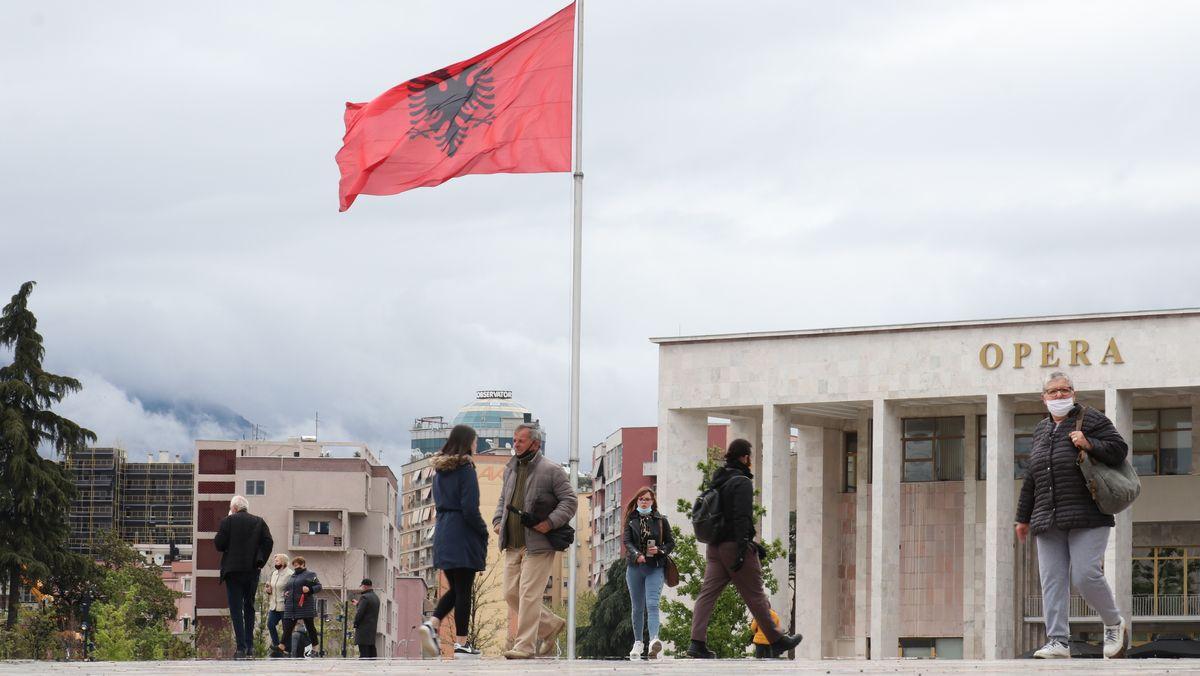 Die albanische Fahne weht in einer Stadtkulisse.