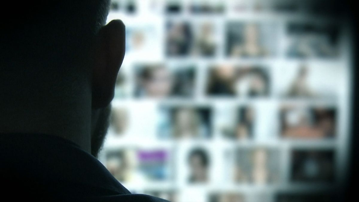 Mann sitzt vor einem Bildschirm mit Fotos (Symbolbild)