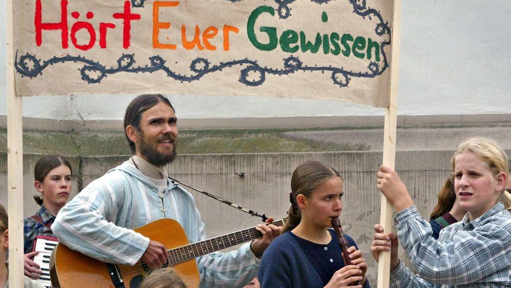 Mitglieder der Zwölf Stämme bei einer Demonstration (Archivbild von 2004)   Bild:pa/Dpa
